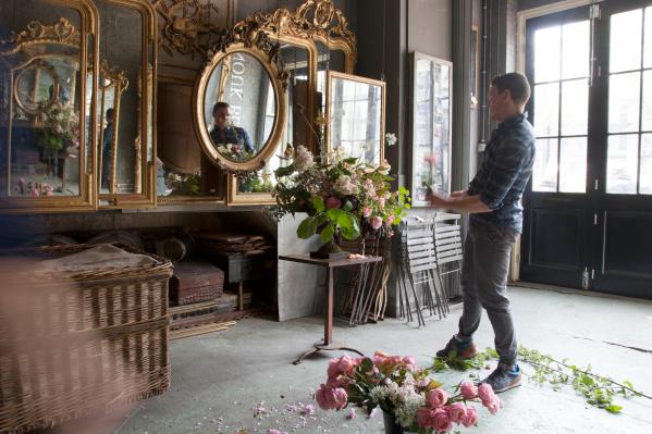 man maakt bloemenstuk voor grote rond spiegel frans