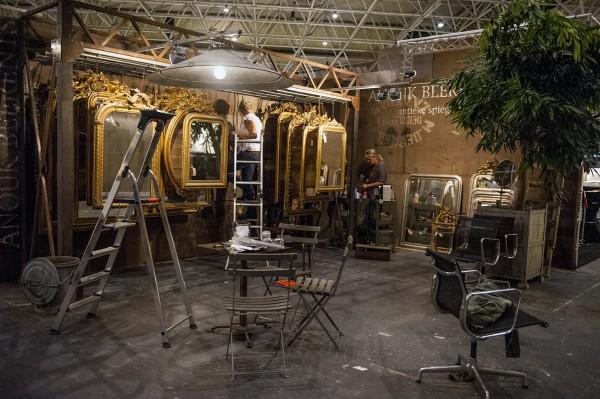 Woonbeurs antieke spiegels ophangen in stand